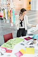 Female fashion designer talking on a mobile phone in an office