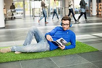 Businessman listening to music and reading book while relaxing on grass mat in an office lobby (thumbnail)