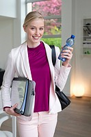 Businesswoman with files and water bottle