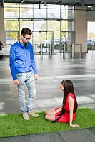 Business executives relaxing on grass mat in an office lobby