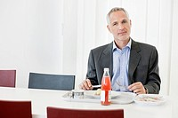Businessman having lunch in the office (thumbnail)