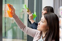 Businesswomen sticking memo notes on glass in an office