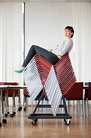 Businesswoman sitting on pileup chairs in an office (thumbnail)