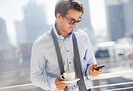 Businessman with coffee checking cell phone on urban balcony (thumbnail)