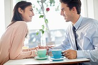 Smiling couple holding hands and drinking coffee in café