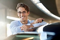 Portrait of smiling businessman leaning on car (thumbnail)