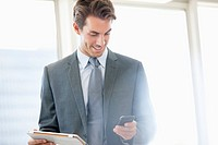 Smiling businessman holding digital tablet and checking cell phone