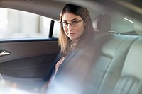 Portrait of confident businesswoman in back seat of car