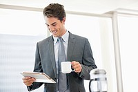 Businessman drinking coffee and looking down at digital tablet