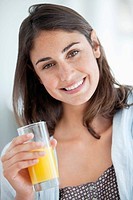 Close up portrait of smiling woman drinking orange juice