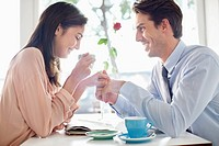Couple drinking coffee and holding hands in café