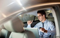 Businessman with cell phone and laptop in back seat of car