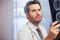 Serious doctor examining x_rays in hospital corridor