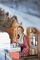 Portrait of smiling woman holding Christmas gifts on cabin porch