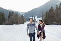 Smiling couple holding hands and walking in snowy field (thumbnail)