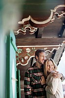 Smiling couple hugging on cabin porch (thumbnail)
