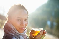Portrait of smiling woman in scarf drinking cider (thumbnail)