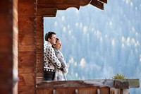 Couple hugging and looking at view from cabin porch (thumbnail)