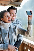 Smiling couple taking self-portrait with camera phone on cabin porch (thumbnail)