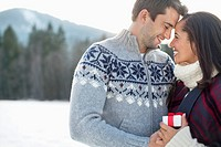 Smiling couple face to face in snowy field (thumbnail)