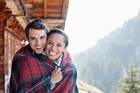 Portrait of smiling couple wrapped in a blanket on cabin porch (thumbnail)