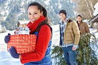 Portrait of friends with fresh cut Christmas tree and gifts in snow (thumbnail)