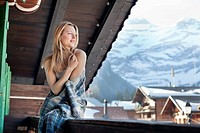 Smiling woman wrapped in a blanket and looking at view on cabin porch