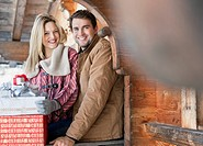 Portrait of smiling couple with Christmas gifts on cabin porch (thumbnail)