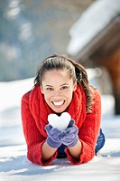 Portrait of smiling woman holding heart_shaped snowball