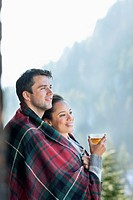 Smiling couple wrapped in a blanket and drinking tea outdoors (thumbnail)