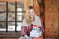 Portrait of smiling woman holding Christmas gifts on cabin porch (thumbnail)