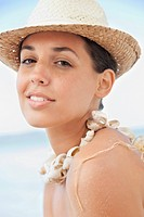 Close up portrait of smiling woman in sun hat at beach