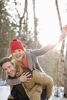 Portrait of smiling couple piggybacking in snow (thumbnail)