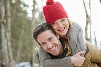 Portrait of smiling couple piggybacking in woods