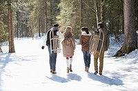Friends with sleds walking in snowy woods
