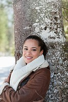 Portrait of smiling woman leaning against tree trunk