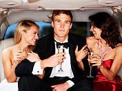 A handsome young celebrity drinking champagne flanked by two gorgeous woman in a limousine