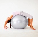 Young woman bending backwards over a physio ball