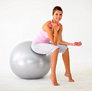 Young woman sitting on a swiss ball and bicep curling dumbbells