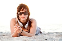Beautiful brunette girl with headphones at beach sand.