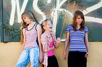 Teenage girls against a graffiti