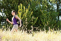 Woman running through meadow