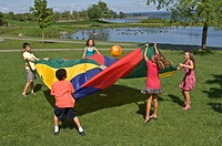 Group Of Children Bouncing A Ball On A Colourful Parachute