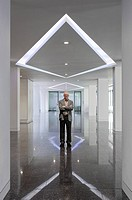 Ken Shuttleworth at 55 Baker Street, London, United Kingdom. Architect: Make Ltd, 2008. Distant view at reception area looking into lens with neutral ...