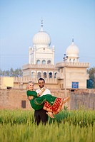 Portrait of a mixed race couple her wearing a sari with a temple in the background, ludhiana punjab india