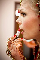 A woman with mehndi jewelry on her hands and applies lipstick, ludhiana punjab india