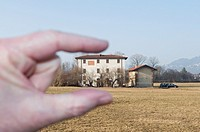 Fingers measuring a country house