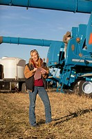 Woman documenting notes with farm equipment in the background, three hills alberta canada