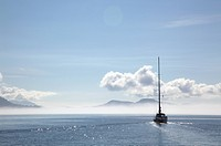 A sailboat cruises on a sunny day in the gulf islands, british columbia canada
