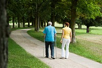 Woman walking with old man in park